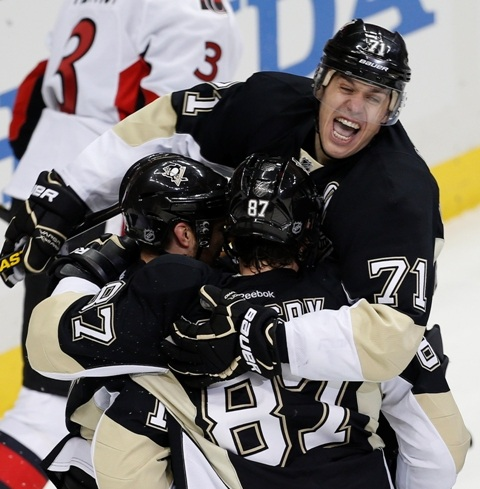 Pittsburgh Penguins' Evgeni Malkin (R) celebrates a goal by teammate Chris Kunitz (L) and Sidney Crosby against the Ottawa Senators during the first period of Game 1 of their NHL Eastern Conference semi-final hockey game in Pittsburgh, Pennsylvania May 14, 2013. REUTERS/Jason Cohn (UNITED STATES  - Tags: SPORT ICE HOCKEY)   - RTXZMR7